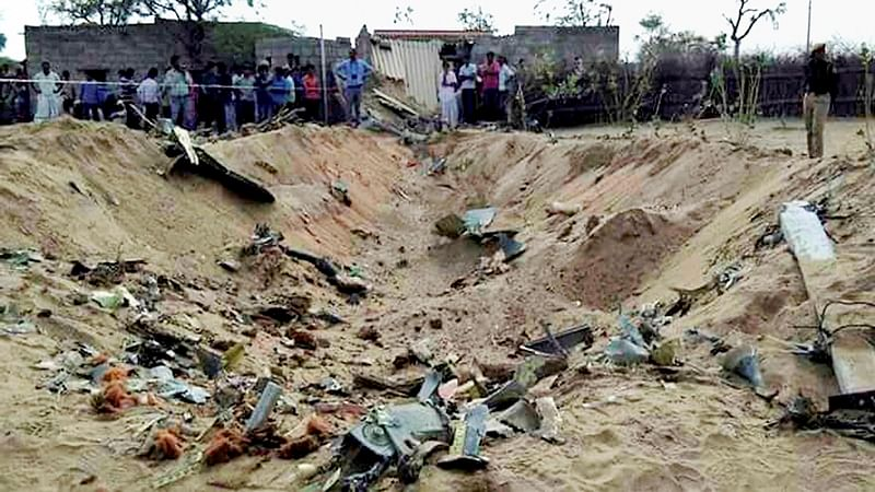 Barmer: People gather near the site in Shivkar Kudla village where an IAF Sukhoi-30 MKI fighter aircraft crashed while on a routine training sortie in Barmer district of Rajasthan on Wednesday. PTI Photo   *** Local Caption ***