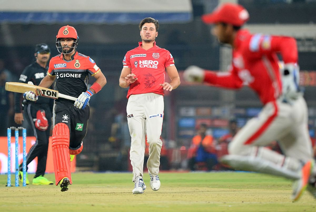 Royal Challengers Bangalore batsman Mandeep Singh (L) runs between the wickets as Kings XI Punjab bowler Marcus Stoinis (C) and wicketkeeper Wriddhiman Saha looks on during the 2017 Indian Premier League (IPL) Twenty20 cricket match between Kings XI Punjab and Royal Challengers Bangalore at the Holkar Stadium in Indore on April 10, 2017. —-IMAGE RESTRICTED TO EDITORIAL USE – STRICTLY NO COMMERCIAL USE—– / AFP PHOTO / SAJJAD HUSSAIN / —-IMAGE RESTRICTED TO EDITORIAL USE – STRICTLY NO COMMERCIAL USE—– / GETTYOUT