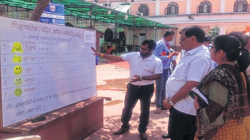 Divisional commissioner checking a board, installed on Mahakaleshwar temple premises to collect feedback on cleanliness arrangements from visitors. FP PHOTO