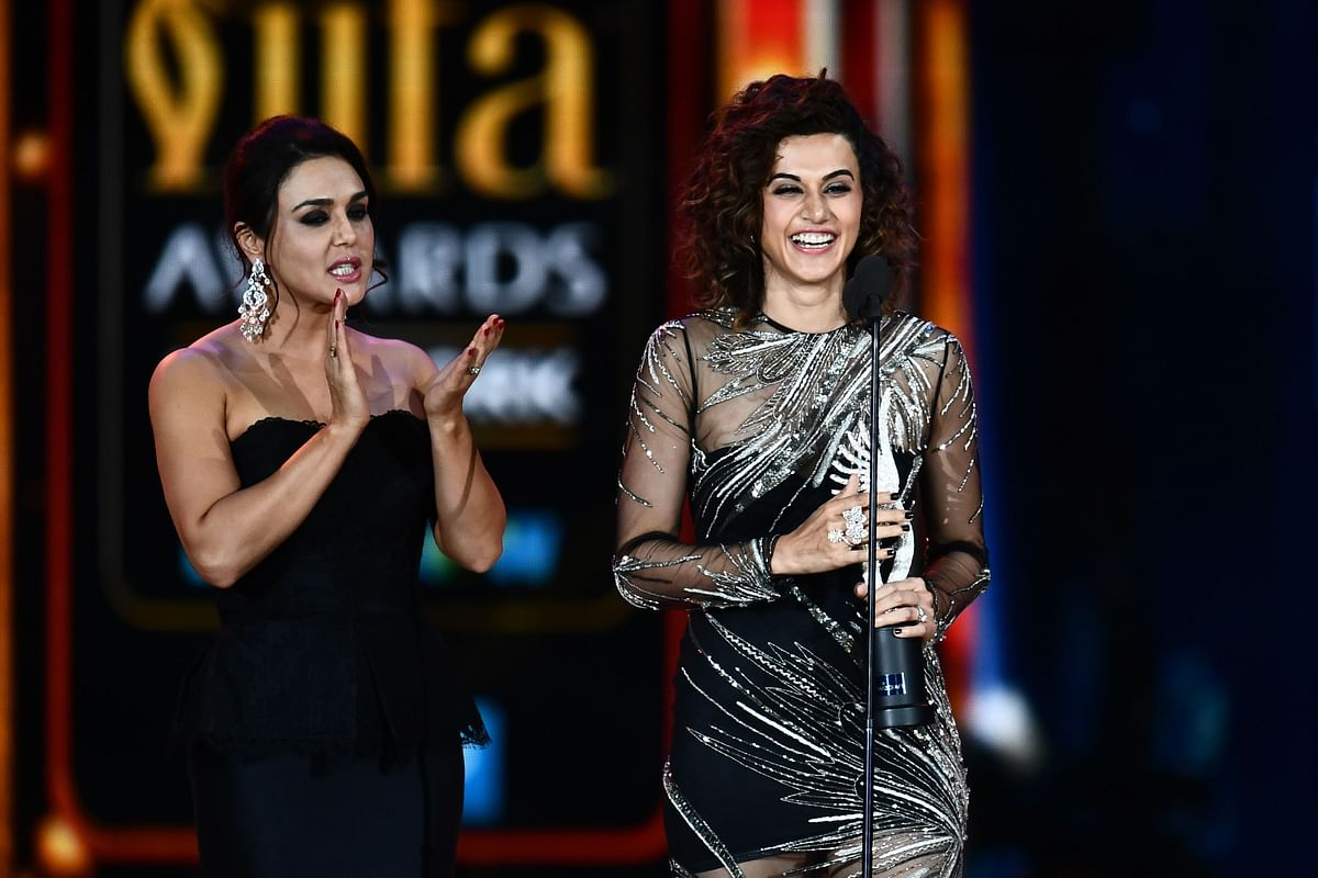 Bollywood actress Taapsee Pannu (R) accepts Women of the Year award from Preity Zinta (L) during IIFA award of the 18th International Indian Film Academy (IIFA) Festival at the MetLife Stadium in East Rutherford, New Jersey, on July 15, 2017. / AFP PHOTO / JEWEL SAMAD