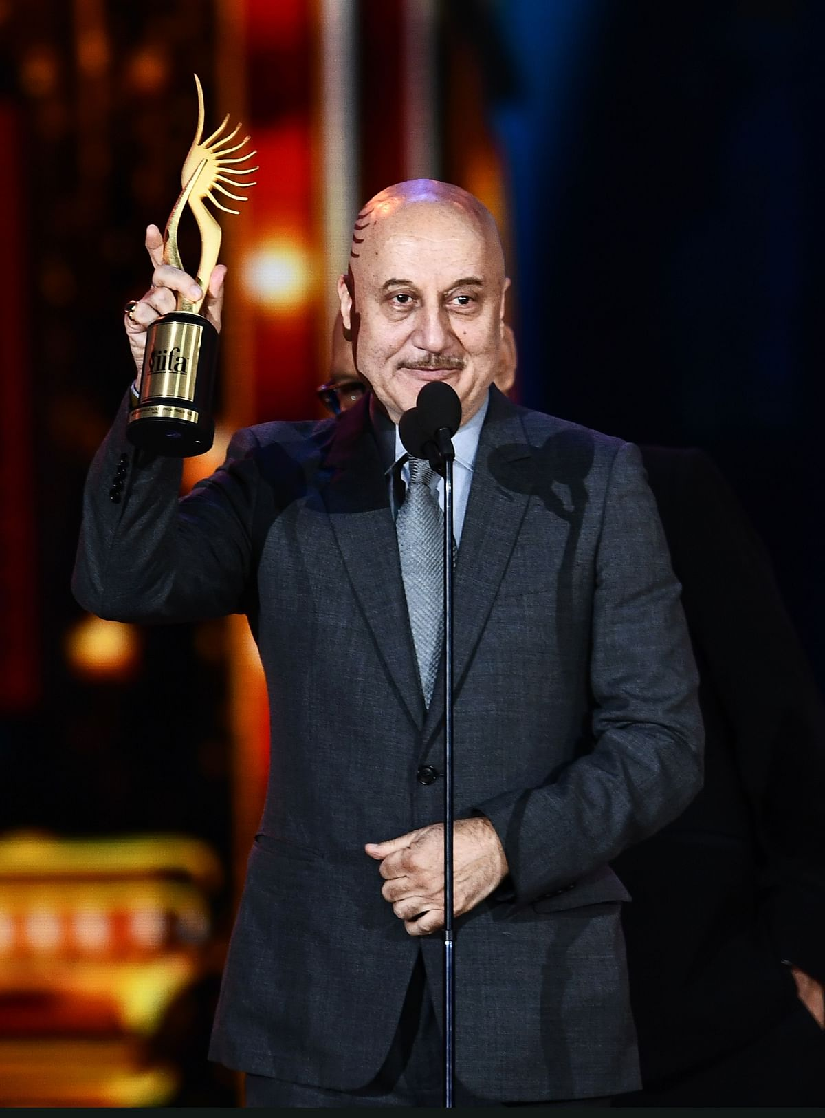 "Winner of Performance in a Supporting Role – Male, Bollywood actor Anupam Kher for ""M.S. Dhoni"" accepts the award during 18th International Indian Film Academy (IIFA) Festival at the MetLife Stadium in East Rutherford, New Jersey, on July 15, 2017. / AFP PHOTO / JEWEL SAMAD"