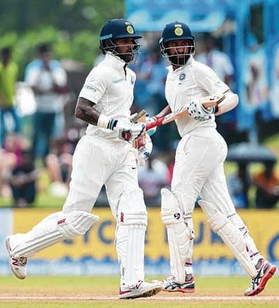 Indian cricketers Shikar Dhawan (L) and Cheteshwar Pujara run between the wickets during the first day of first Test match between Sri Lanka and India at Galle International Cricket Stadium in Galle on July 26, 2017. / AFP PHOTO / ISHARA S. KODIKARA