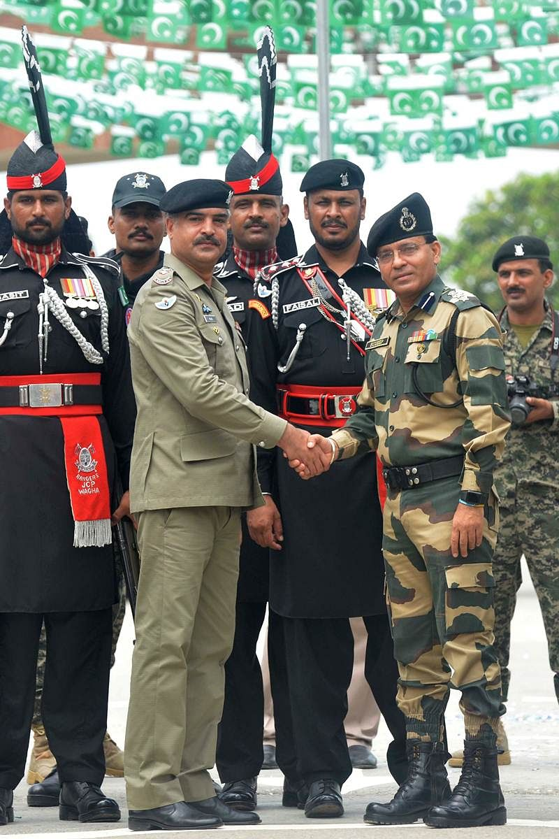 Pakistani Wing Commander Bilal (2L) shakes hand with the Indian Border Security Force (BSF) Commandant Sudeep (2R) during a ceremony to celebrate Pakistan's Independence Day at the India-Pakistan Wagah border post on August 14, 2017. / AFP PHOTO / NARINDER NANU