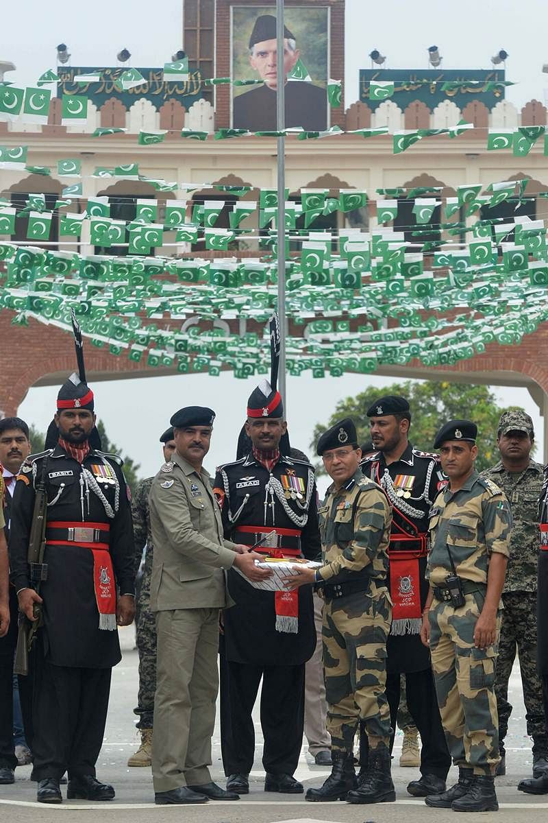 Pakistani Wing Commander Bilal (2L) presents sweets to presents sweets to Indian Border Security Force (BSF) Commandant Sudeep (4R) during a ceremony to celebrate Pakistan's Independence Day at the India-Pakistan Wagah border post on August 14, 2017. / AFP PHOTO / NARINDER NANU