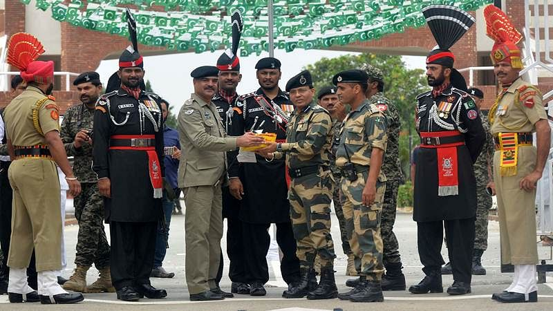 Pakistani Wing Commander Bilal (4L) presents sweets to Indian Border Security Force (BSF) Commandant Sudeep (4R) during a ceremony to celebrate Pakistan's Independence Day at the India-Pakistan Wagah border post on August 14, 2017. / AFP PHOTO / NARINDER NANU