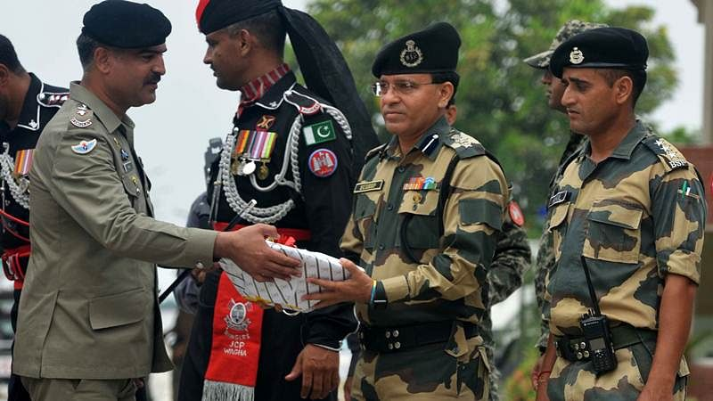 Pakistani Wing Commander Bilal (L)presents sweets to Indian Border Security Force (BSF) Commandant Sudeep (2R) during a ceremony to celebrate Pakistan's Independence Day at the India-Pakistan Wagah border post on August 14, 2017. / AFP PHOTO / NARINDER NANU
