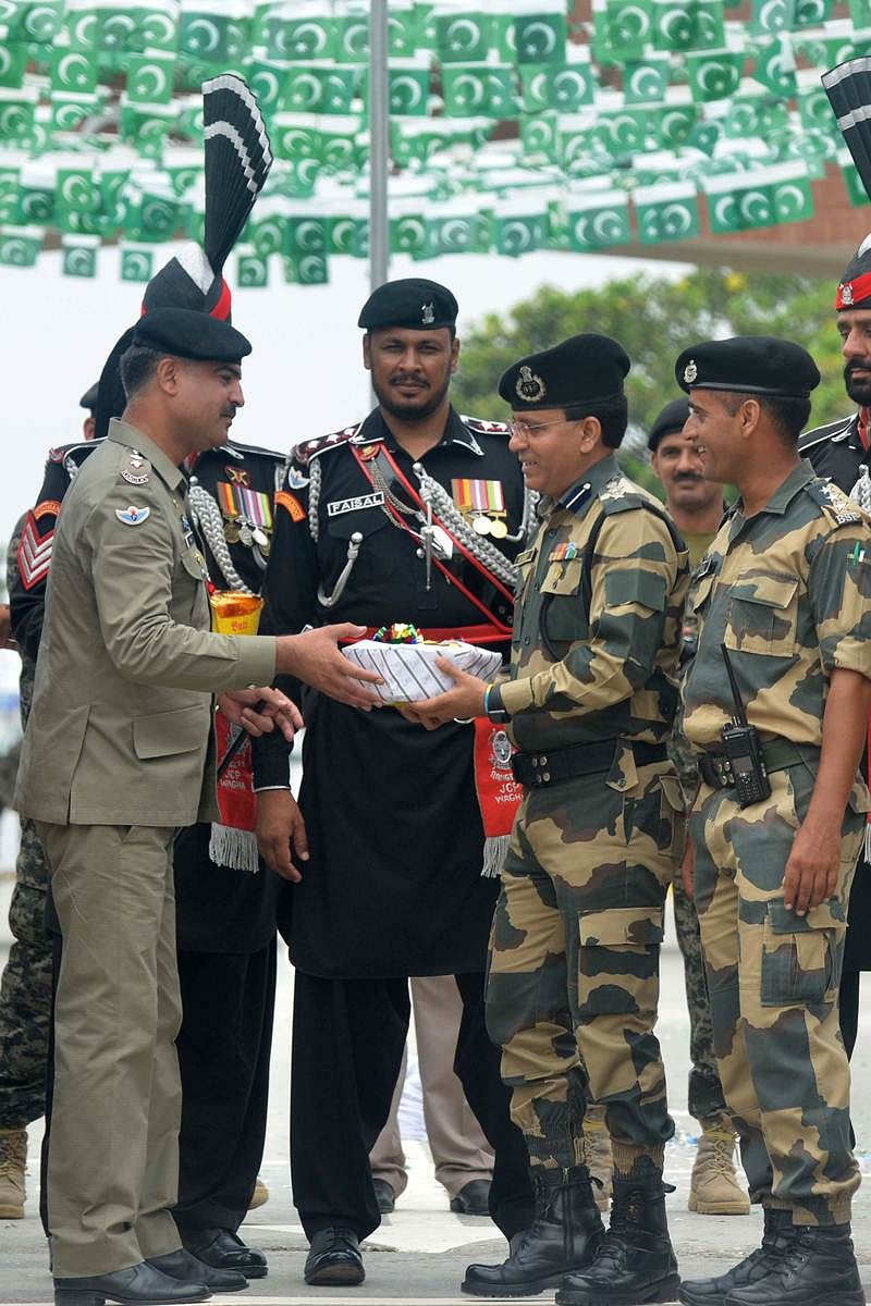 Pakistani Wing Commander Bilal (L) presents sweets to Indian Border Security Force (BSF) Commandant Sudeep (2R) during a ceremony to celebrate Pakistan's Independence Day at the India-Pakistan Wagah border post on August 14, 2017. / AFP PHOTO / NARINDER NANU
