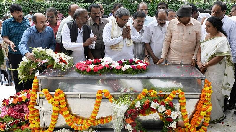 Chief Minister of Karnataka Siddaramaiah (C) along with senior politicians from the state pay their respects next to her body at the Ravindra Kalakshetra cultural centre in Bangalore on September 6, 2017. / AFP PHOTO / MANJUNATH KIRAN