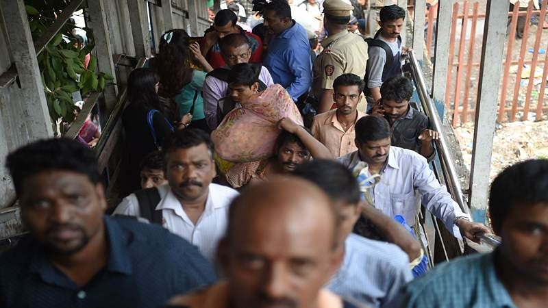 Indian pedestrians walk through the scene of a stampede on a railway bridge in Mumbai