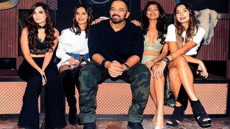 Indian Bollywood director Rohit Shetty (C) and contestants pose for a photograph during a promotional event for the 'Khatron Ke Khiladi' reality show, based on the US format 'Fear Factor' in Mumbai on late September 19, 2017. / AFP PHOTO / STR