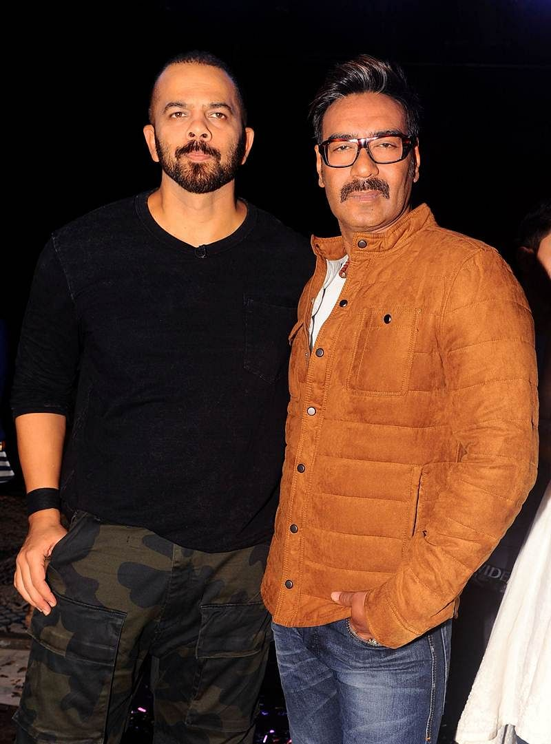 Indian Bollywood director Rohit Shetty (L) and actor Ajay Devgn pose for a photograph during a promotional event for the 'Khatron Ke Khiladi' reality show, based on the US format 'Fear Factor' in Mumbai on late September 19, 2017. / AFP PHOTO / STR