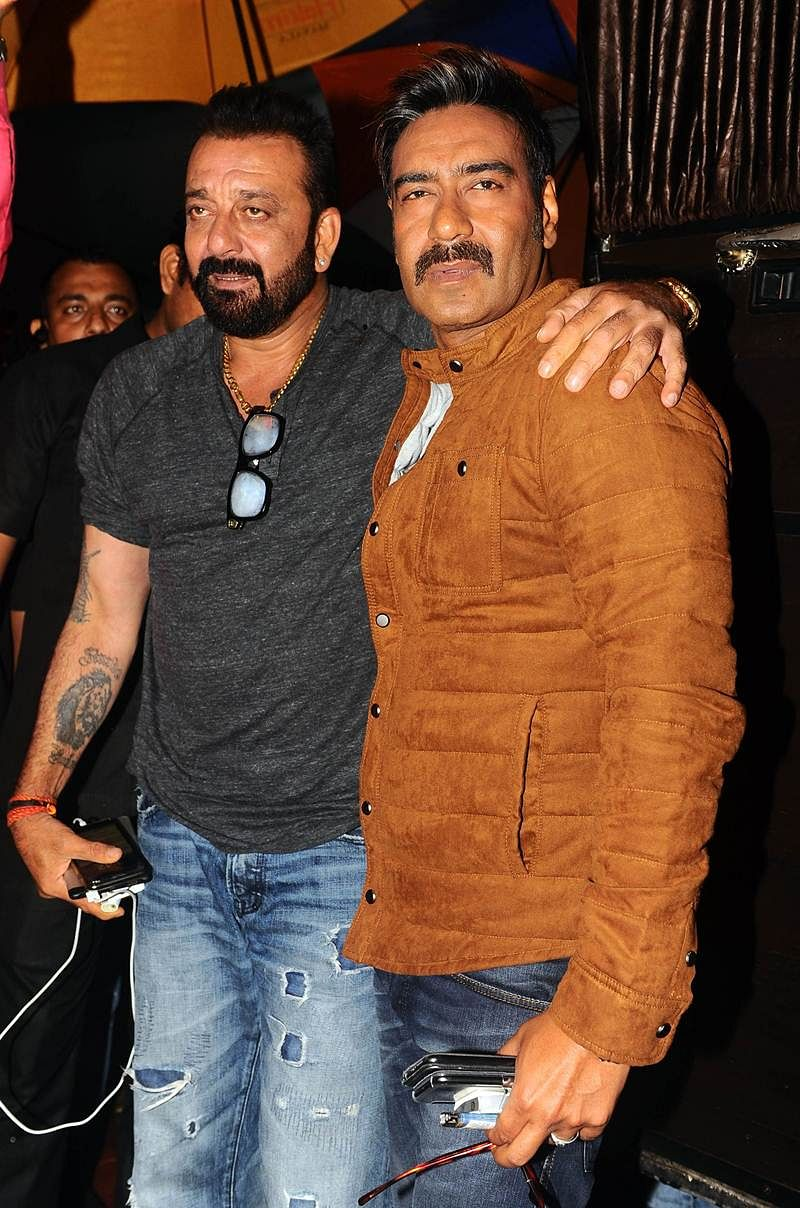 Indian Bollywood actors Sanjay Dutt (L) and Ajay Devgn pose for a photograph during a promotional event for the 'Khatron Ke Khiladi' reality show, based on the US format 'Fear Factor' in Mumbai on late September 19, 2017. / AFP PHOTO / STR