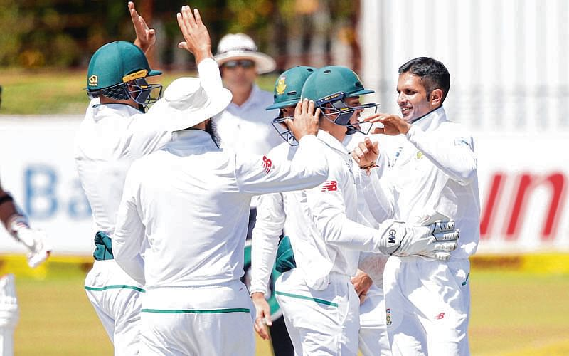 South African bowler Keshav Maharaj (R) celebrates the dismissal of Bangladesh batsman Sabbir Rahman (not in picture) during the fifth day of the Test Match between South Africa and Bangladesh on October 2, 2017 in Potchefstroom.   / AFP PHOTO / GIANLUIGI GUERCIA