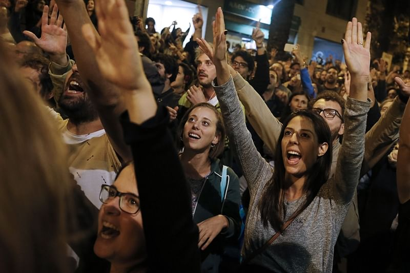 People celebrate after the closing of the 'Espai Jove La Fontana' (La Fontana youth center) polling station, on October 1, 2017 in Barcelona.  Spanish riot police stormed voting stations today as they moved to stop Catalonia's independence referendum after it was banned by the central government in Madrid. At least 92 people were confirmed injured as hundreds tried to prevent the polling stations from being closed, Catalan officials said. A total of 465 people were treated at hospitals and health centres, while Spain's interior ministry said 12 police officers were injured.  / AFP PHOTO / PAU BARRENA
