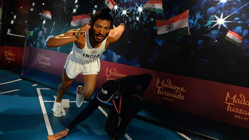 An employee cleans the floor near the wax statue of former Indian track and field sprinter Milkha Singh during the launch of Madame Tussauds Delhi.