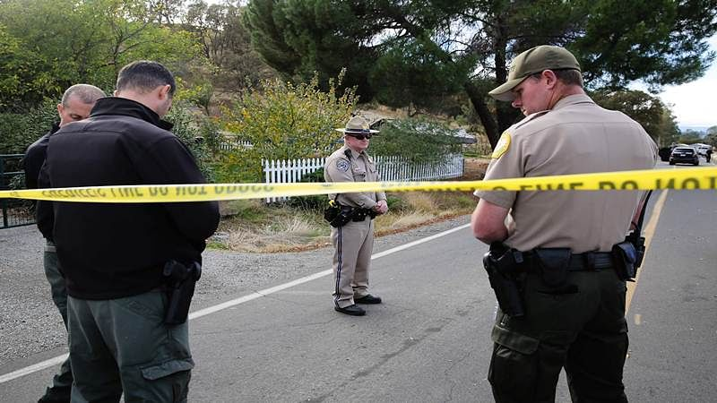 Law enforcement officers stand near one of many crime scenes after a shooting on November 14, 2017, in Rancho Tehama, California Four people were killed and nearly a dozen were wounded, including several children, when a gunman went on a rampage at multiple locations, including a school in rural northern California. / AFP PHOTO / Elijah Nouvelage