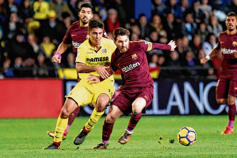 Villarreal's midfielder Rodrigo Hernandez (L) vies with Barcelona's Argentinian forward Lionel Messi during the Spanish league football match between Villarreal CF and FC Barcelona at La Ceramica stadium in Vila-real on December 10, 2017. / AFP PHOTO / JOSE JORDAN