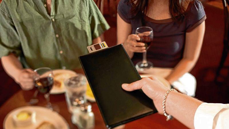 Waitress handing bill to couple in restaurant