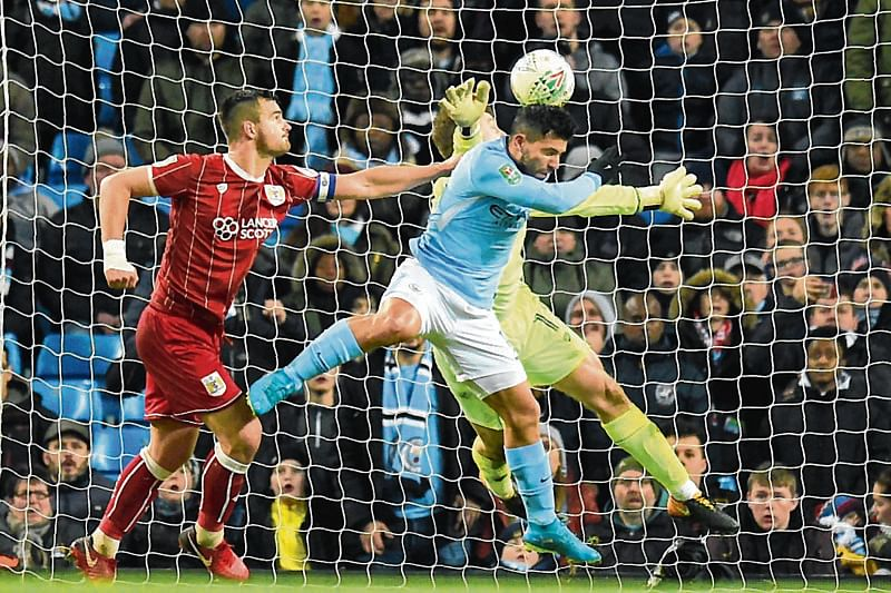 TOPSHOT - Manchester City's Argentinian striker Sergio Aguero (C) jumps to score their late winning goal during the English League Cup semi-final first leg football match between Manchester City and Bristol City at the Etihad Stadium in Manchester, north west England, on January 9, 2018. Manchester City won the game 2-1. / AFP PHOTO / Oli SCARFF / RESTRICTED TO EDITORIAL USE. No use with unauthorized audio, video, data, fixture lists, club/league logos or 'live' services. Online in-match use limited to 75 images, no video emulation. No use in betting, games or single club/league/player publications.  /
