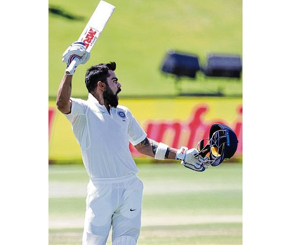 India's captain Virat Kohli raises his bat and helmet as he celebrates scoring a century (100 runs) during the third day of the second Test cricket match between South Africa and India at Supersport cricket ground on January 15, 2018 in Centurion, South Africa.  / AFP PHOTO / GIANLUIGI GUERCIA