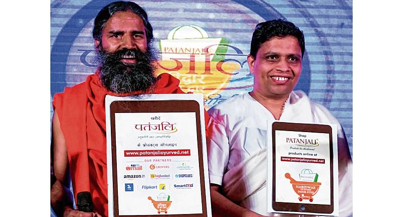 Indian yoga guru Baba Ramdev (L) and Patanjali Ayurveda Managing Director, Acharya Balkrishna (R)
