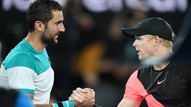 Marin Cilic (L) is congratulated by Britain's Kyle Edmund after their singles semi-finals match of the Australian Open. / AFP PHOTO / SAEED KHAN