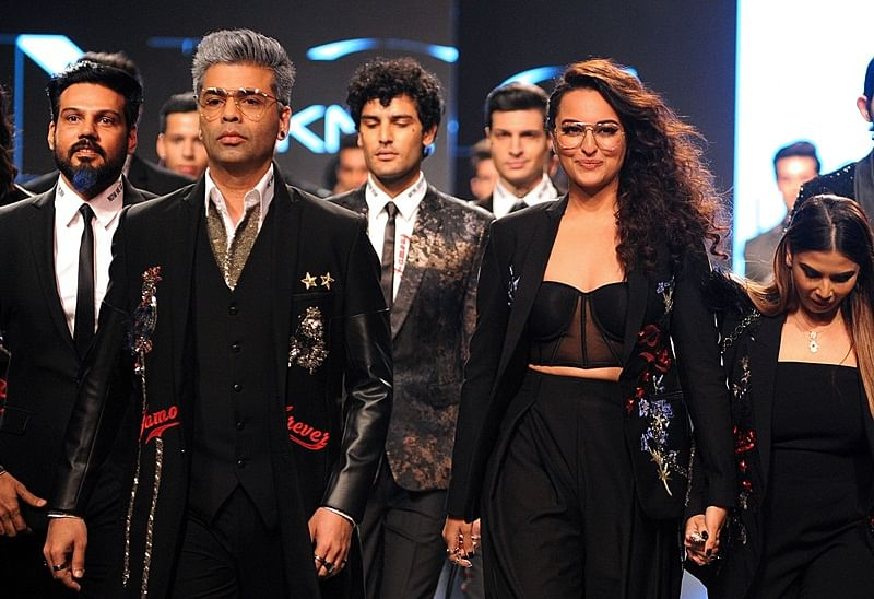 Indian Bollywood film director Karan Johar (L) and actress Sonakshi Sinha (R) showcase creations by designer Falguni Shane Peacock at the Lakmé Fashion Week (LFW) Summer Resort 2018 in Mumbai on February 2, 2018.