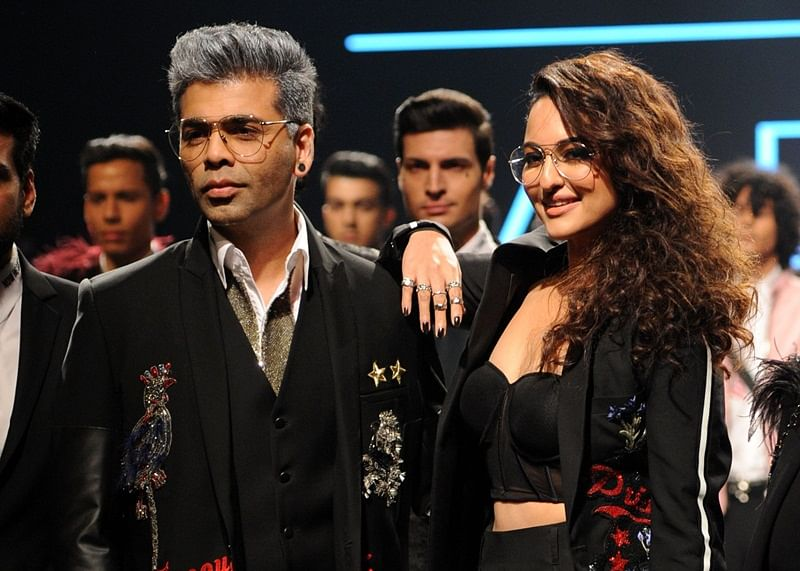 Indian Bollywood film director Karan Johar (L) and actress Sonakshi Sinha (R) showcase creations by designer Falguni Shane Peacock at the Lakmé Fashion Week (LFW) Summer Resort 2018 in Mumbai on February 2, 2018. /