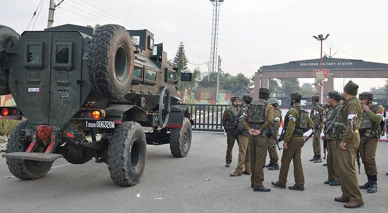 Security personnel stand guard outside the Sunjuwan Army camp during the encounter in Jammu. PTI Photo
