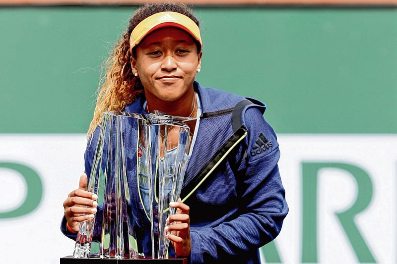 INDIAN WELLS, CA - MARCH 18: Naomi Osaka of Japan poses with the winner's trophy after defeating Daria Kasatkina of Russia during the women's final on Day 14 of the BNP Paribas Open at the Indian Wells Tennis Garden on March 18, 2018 in Indian Wells, California.   Matthew Stockman/Getty Images/AFP == FOR NEWSPAPERS, INTERNET, TELCOS & TELEVISION USE ONLY ==
