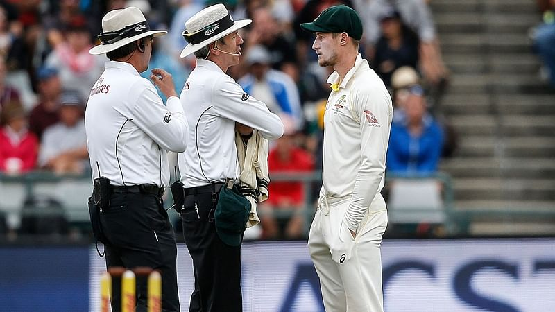 Cameron Bancroft (R) questioned by Umpires Richard Illingworth (L) and Nigel Llong (C) during the third Test against South Africa. / FILE PHOTO / GIANLUIGI GUERCIA