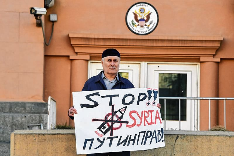 "TOPSHOT - A man holds a banner supporting Syria and read as ""Putin is right!"" in front of US embassy in central Moscow on April 14, 2018.  The UN Security Council will meet on April 14 at Russia's request to discuss air strikes launched by the United States, France and Britain on Moscow-allied Syria in response to a suspected chemical weapons attack. / AFP PHOTO / Vasily MAXIMOV"