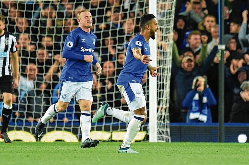 Everton's English striker Theo Walcott (R) celebrates scoring the opening goal during the English Premier League football match between Everton and Newcastle United at Goodison Park in Liverpool, north west England on April 23, 2018. / AFP PHOTO / Oli SCARFF / RESTRICTED TO EDITORIAL USE. No use with unauthorized audio, video, data, fixture lists, club/league logos or 'live' services. Online in-match use limited to 75 images, no video emulation. No use in betting, games or single club/league/player publications.  /