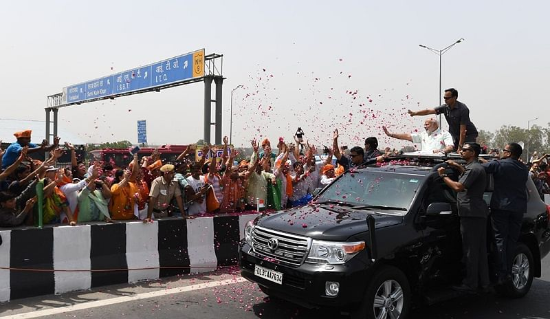 "This handout photograph taken by India's Press Information Bureau (PIB) on May 27, 2018 shows India's Prime Minister Narendra Modi waving from atop a car during the inauguration of the Delhi-Meerut Expressway, in Delhi. / AFP PHOTO / PIB / Handout / RESTRICTED ""AFP PHOTO / PIB"""