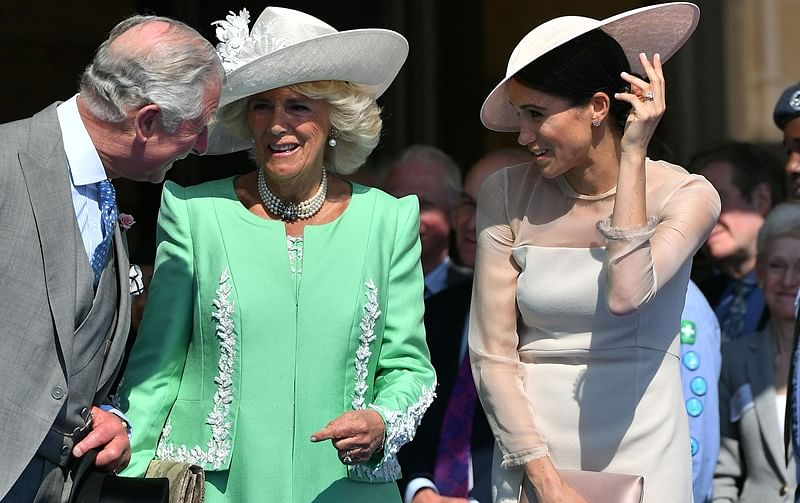 Britain's Prince Charles, Prince of Wales (L) and his wife Britain's Camilla, Duchess of Cornwall (C), talk with Britain's Meghan, Duchess of Sussex, as her husband Britain's Prince Harry, Duke of Sussex (unseen). / AFP PHOTO / POOL / Dominic Lipinski