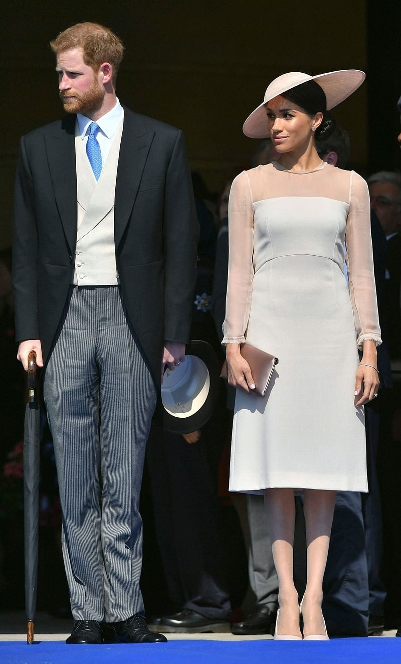 London : Meghan, the Duchess of Sussex stands with her husband, Prince Harry as they attend a garden party at Buckingham Palace in London. AP/PTI