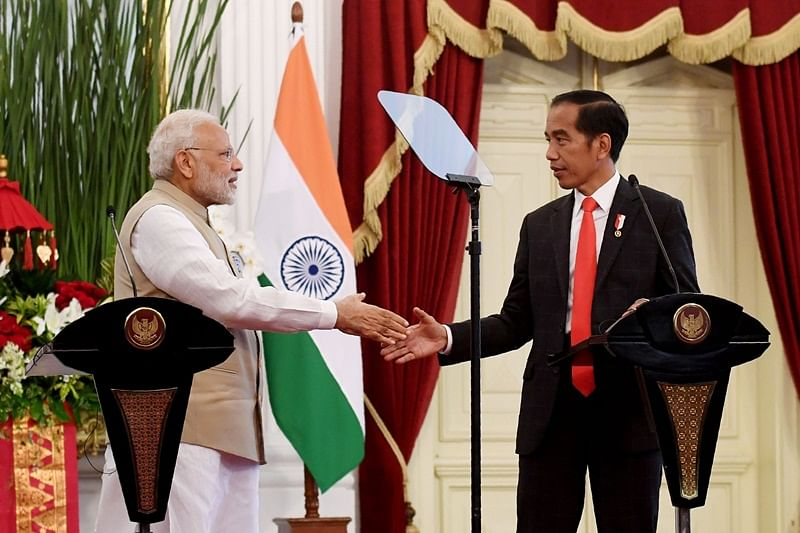 Indonesia's President Joko Widodo (R) shakes hands with India's Prime Minister Narendra Modi during a joint press conference at the presidential palace in Jakarta on May 30, 2018.  / AFP PHOTO / Goh Chai Hin