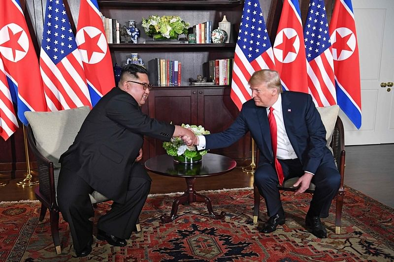 US President Donald Trump (R) shakes hands with North Korea's leader Kim Jong Un (L) as they sit down for their historic US-North Korea summit, at the Capella Hotel on Sentosa island in Singapore on June 12, 2018. Donald Trump and Kim Jong Un have become on June 12 the first sitting US and North Korean leaders to meet, shake hands and negotiate to end a decades-old nuclear stand-off. / AFP PHOTO / SAUL LOEB