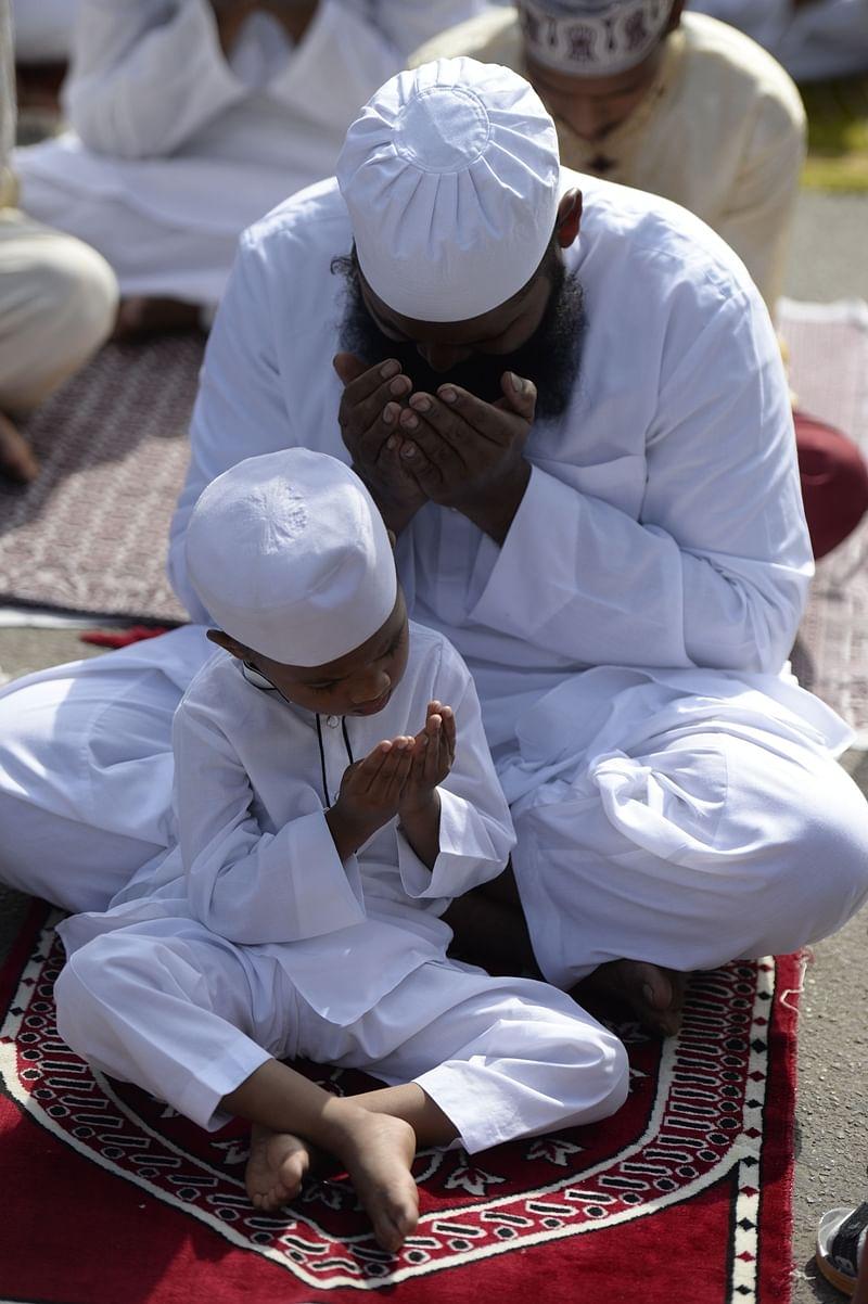 Indian Muslims offer Eid al-Fitr prayers outside Eidgah-Bilal, in Hyderabad on June 16, 2018./ AFP PHOTO / NOAH SEELAM
