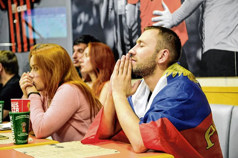 Russia supporters react as they watch the Russia 2018 World Cup quarter-final football match between Russia and Croatia on a screen at a fan cafe at the Donbass Arena Stadium in Donetsk on July 7, 2018. Scores of Russia-supporting fans gathered in a cafe inside the disused Donbass Arena in conflict-stricken eastern Ukraine to watch their favoured team play Croatia in the World Cup on July 7. Some came with Russian flags in support of the country which they consider to be their homeland, jumping up and applauding until Croatia finally prevailed on penalties. / AFP PHOTO / Sega VOLSKII