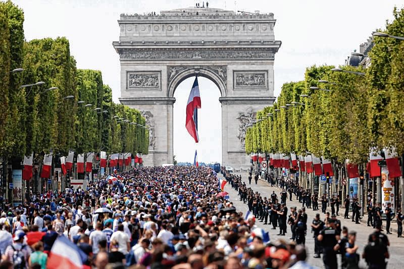 Supporters gather on the Champs-Elysees avenue near the Arch of Triumph (Arc de Triomphe) in Paris on July 16, 2018 as they wait for the arrival of the French national football team for celebrations after France won the Russia 2018 World Cup final football match on the previous night. / AFP PHOTO / Zakaria ABDELKAFI