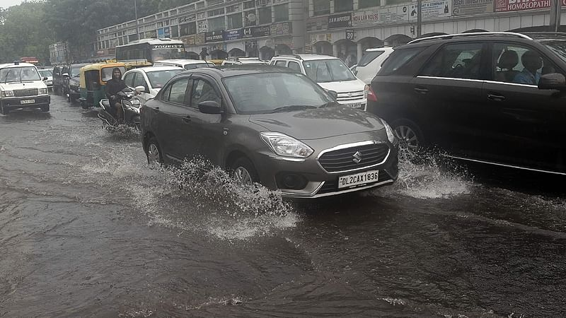 Vehicles drive along a water-logged road during heavy monsoon rain in New Delhi. / AFP PHOTO / PRAKASH SINGH