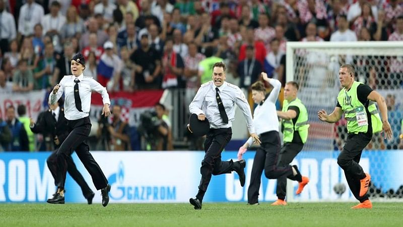Soccer Football - World Cup - Final - France v Croatia - Luzhniki Stadium, Moscow, Russia - July 15, 2018  Stewards chase pitch invaders        REUTERS/Carl Recine