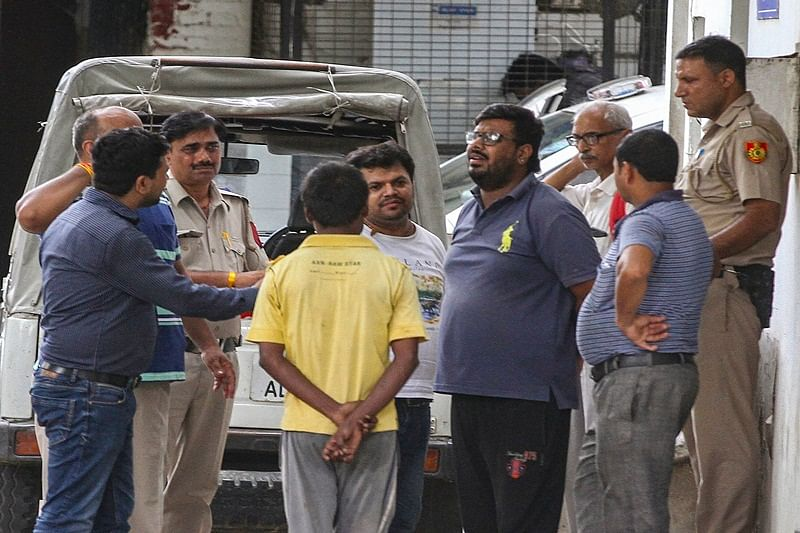 New Delhi: A family member of the 75-year old woman who was among the 11 members of a family found dead at a house in Burari, speaks with police personnel outside Maulana Azad Hospital Mortuary, in New Delhi on Monday, July 02, 2018. (PTI Photo) (PTI7_2_2018_000183B)