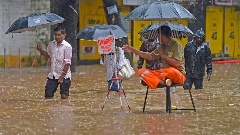Mumbai: A municipal employee warns pedestrians about an open manhole as water floods the streets during heavy rainfall, in Mumbai on Tuesday, July 03, 2018. (PTI Photo/Shashank Parade) (PTI7_3_2018_000144B)