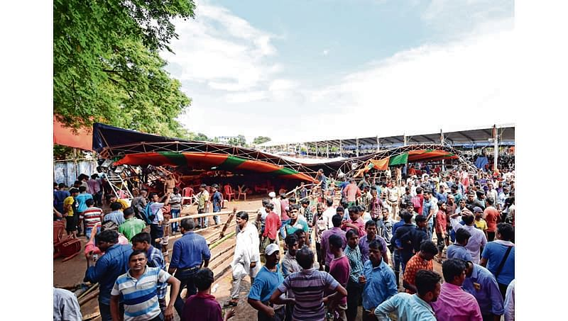 Supporters of Bhartiya Janta Party (BJP) stand next to a damaged tent, which collapsed during a public meeting addressed by India's Prime Minister Narendra Modi (unpictured), at a college ground in Midnapore on July 16, 2018.   15 people were injured on July 16 at a public rally for Narendra Modi after a tent collapsed on the Indian prime minister's audience, police said. / AFP PHOTO / -
