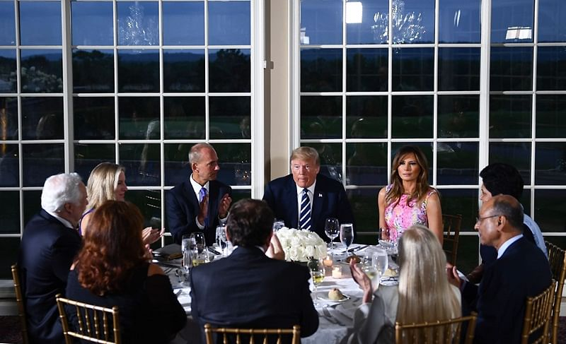 US President Donald Trump (C) sits with First Lady Melania Trump (R) and Boeing CEO Dennis Muilenburg (C-L) and other guests during a dinner with business leaders in Bedminster, New Jersey, on August 7, 2018. / AFP PHOTO / Brendan Smialowski