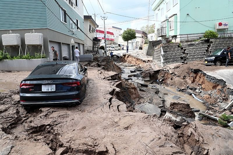 A car is seen stuck on a road damaged by an earthquake in Sapporo, Hokkaido prefecture on September 6, 2018. - A powerful 6.6-magnitude quake rocked the northern Japanese island of Hokkaido on September 6, triggering landslides, collapsing buildings, and killing at least two people with several dozen missing. (Photo by JIJI PRESS / JIJI PRESS / AFP) /