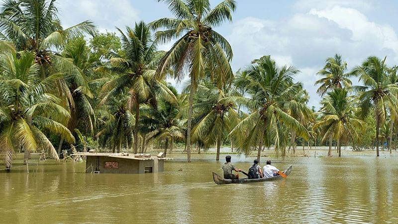 Indian men take a small boat to travel across flood waters past a marooned farm building to reach their homes in Kerala
