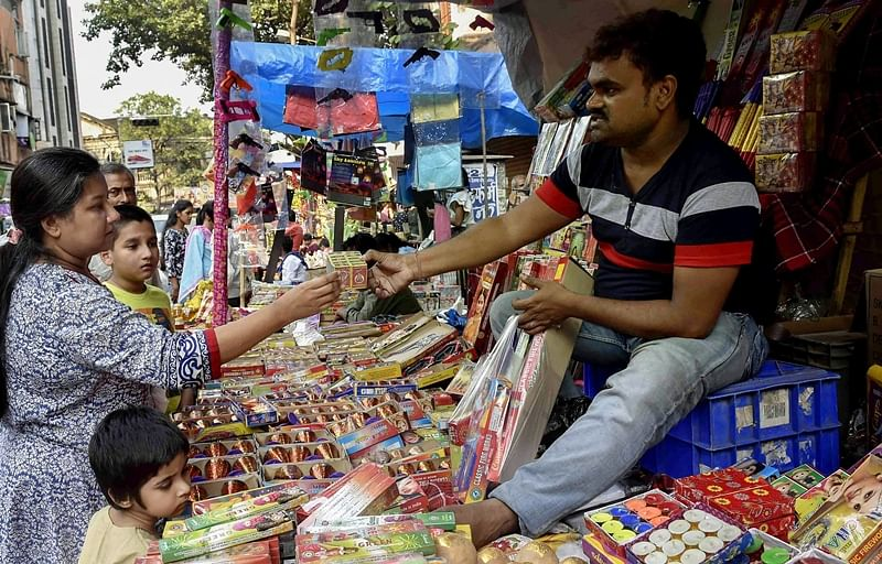 People purchase firecrackers and other items for Diwali festivals, at a shop. PTI Photo/Ashok Bhaumik